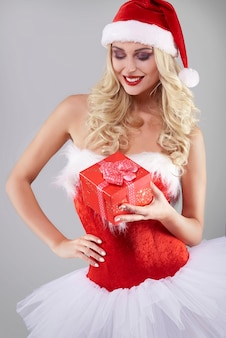 Sexy woman in santa costume on grey wall