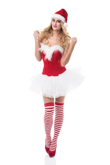 Sexy woman in santa costume posing on white wall