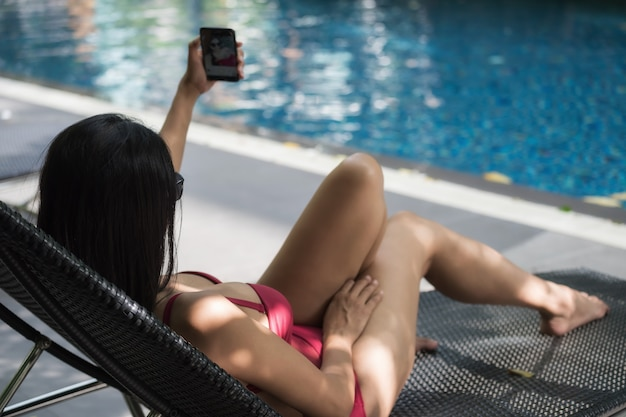 Sexy woman selfie by smartphone at pool