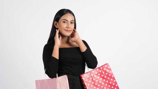 Сексуальная женщина покупок. красивая девушка в черном держит красные хозяйственные сумки, изолированные на белом