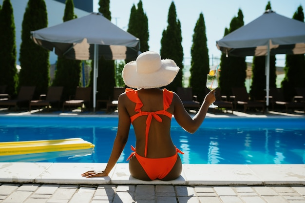 Sexy woman sitting at the edge of the pool, back view. happy people having fun on summer vacations, holiday party at the poolside outdoors. female person leisures at the resort
