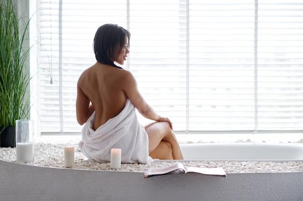 お風呂の端に座っているセクシーな女性、背面図。バスタブの女性、スパの美容とヘルスケア、バスルームのウェルネストリートメント、背景の小石とキャンドル