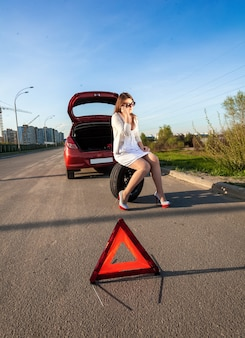 Sexy woman sitting on spare wheel against of broken car and warning sign
