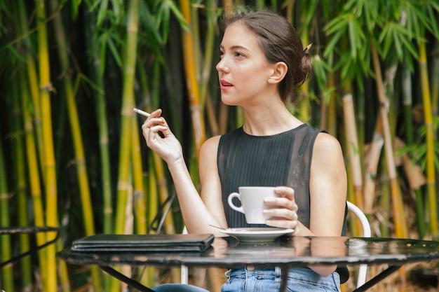 Сексуальная женщина курит и пьет кофе во франции
