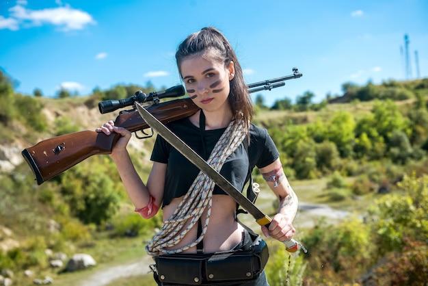 자연 속에서 멀리 보고 소총을 들고 섹시 한 여자 군인. 여전사