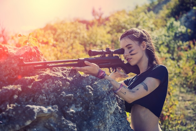 Sexy woman soldier holding a rifle looking away in the nature. female warrior