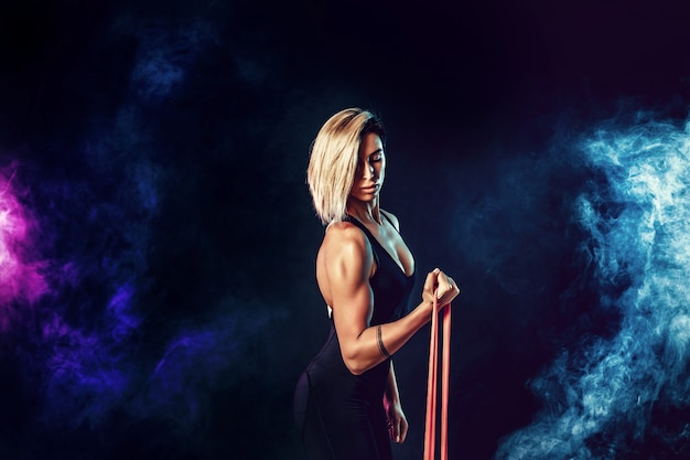 Sexy woman in sportswear using a resistance band in her exercise routine. young woman performs fitness exercises on black wall with smoke. isolate