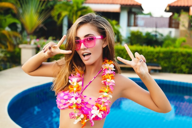 Donna sexy in vacanza estiva divertendosi in piscina indossando bikini e occhiali da sole rosa, fiori tropicali, colorato stile moda estiva