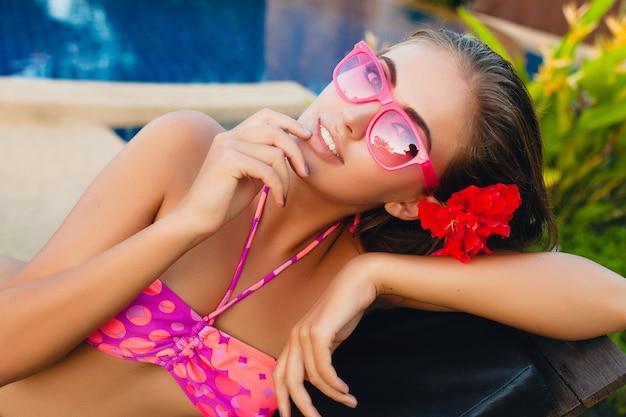 Donna sexy in vacanza estiva sdraiata in piscina indossando bikini e occhiali da sole rosa, fiori tropicali, colorato stile moda estiva