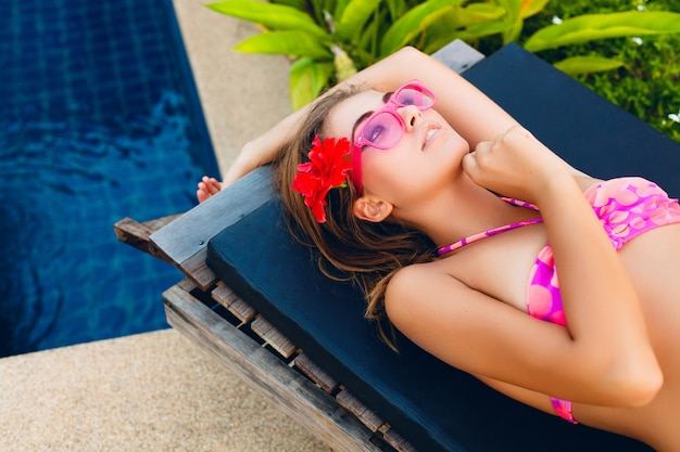 Sexy woman on summer vacation lying at pool wearing bikini and pink sunglasses, tropical flowers, colorful summer fashion style