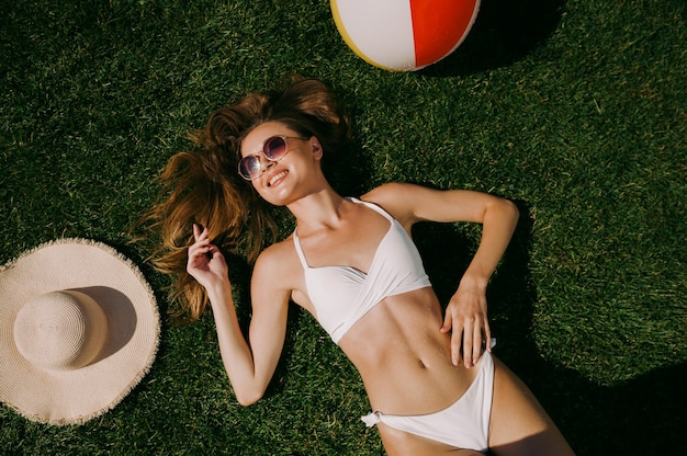 Sexy woman sunbathing on the grass, top view