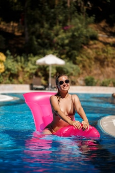 Sexy woman in sunglasses with a smile on her face in a swimsuit lies on a pink inflatable mattress in the pool. relax by the pool on a hot summer sunny day. vacation concept