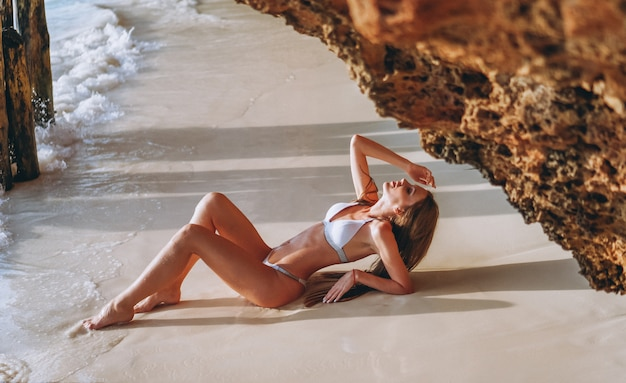 Sexy woman in swim wear lying by the ocean under the caves