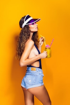 Sexy woman in swimsuit and blue jeans shorts, trendy visor holding glass of fresh drink while standing on yellow, orange hot scene