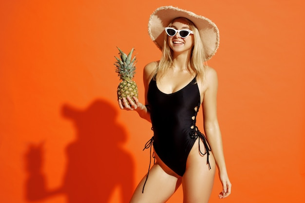Sexy woman in swimsuit poses with pineapple on orange