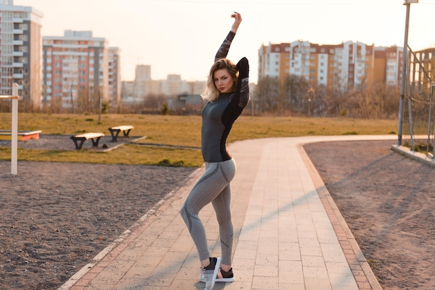 Sexy woman in tight-fitting gray sportswear posing to the camera. healthy lifestyle concept.