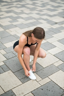 Sexy woman tying her laces high angle shot
