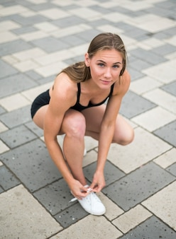 Sexy woman tying her laces high angle view