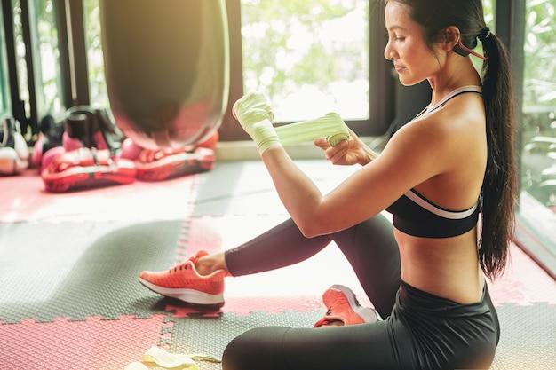 Сексуальная женщина, завязывающая ленту вокруг руки, прежде чем получить боксерские перчатки, готовится к тренировке по боксу