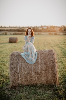 Sexy woman in underwear posing on a haystack in summer at sunset in nature. added the effect of a small film grain