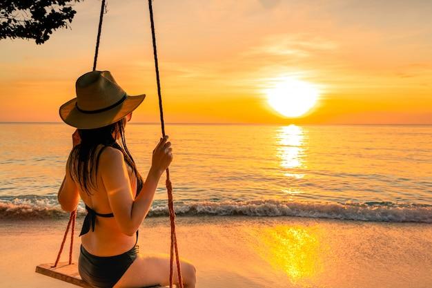 セクシーな女性はビキニを着、麦わら帽子は日没で夏休みに熱帯のビーチでブランコを振る。