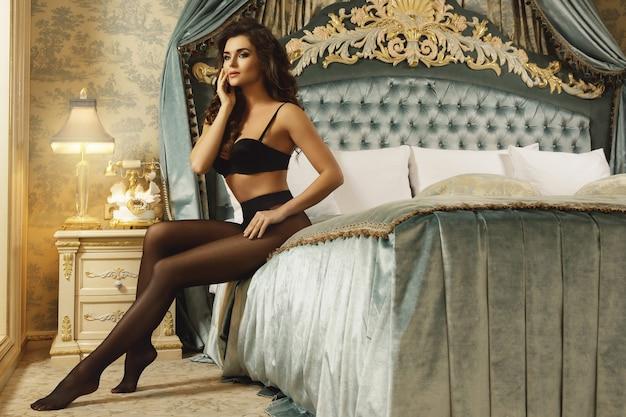 美しいランジェリーと黒のタイツを着ているセクシーな女性