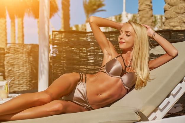 Сексуальная женщина в бикини сидит на шезлонге под соломенным зонтиком на пляже
