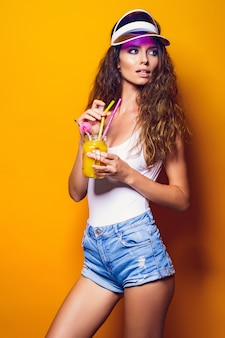 Sexy woman in white swimsuit and blue jeans shorts, trendy visor holding beverage