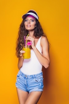 Sexy woman in white swimsuit and blue jeans shorts, trendy visor holding glass of fresh drink while standing on yellow, orange hot