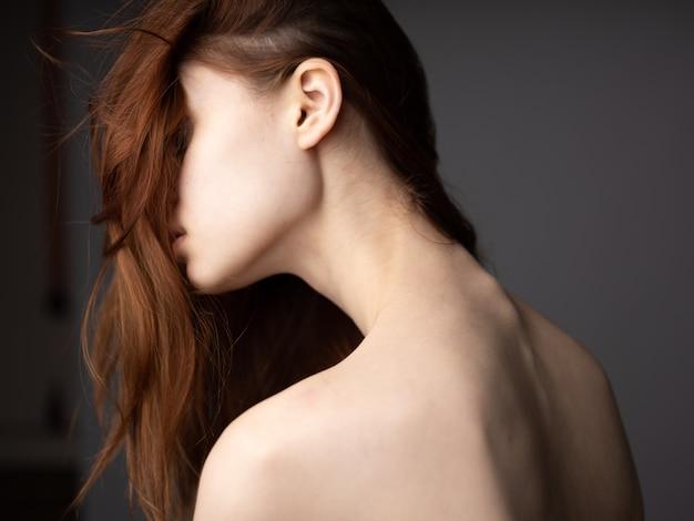회색 배경에 빨간 머리 다시보기에 벌 거 벗은 뒤를 가진 섹시 한 여자. 고품질 사진