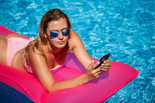 수영복을 입은 섹시한 여성이 수영장에 있는 분홍색 매트리스 위에 놓여 있습니다. 더운 여름 화창한 날 수영장 옆에서 휴식을 취하십시오. 휴가 개념