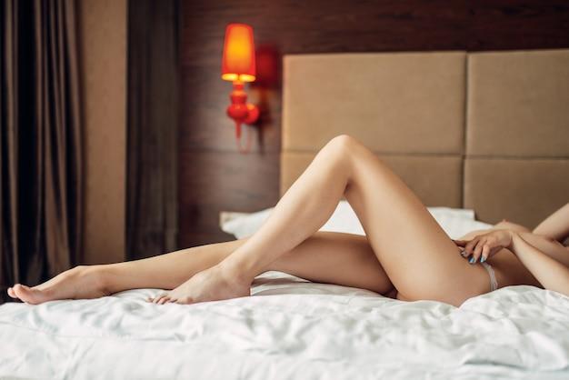 침대에 누워 벌거 벗은 가슴을 가진 섹시한 여자