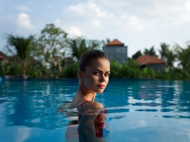 裸の肩を持つセクシーな女性は、澄んだ水のエキゾチックなモデルのプールに立っています