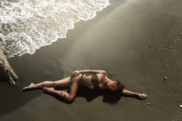 Sexy woman with beautiful body is lying on the beach