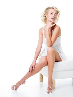 Сексуальная женщина с красивыми ногами сидит на белом стуле