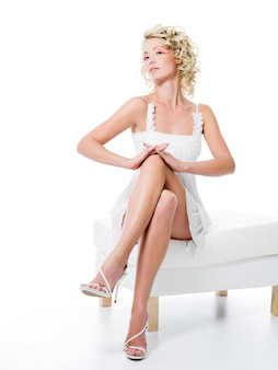Sexy woman with beauty legs sits on white chair