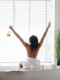 浴槽の端に座っているボトルを持つセクシーな女性、背面図。バスタブの女性、スパの美容とヘルスケア、バスルームのウェルネストリートメント、背景の小石とキャンドル