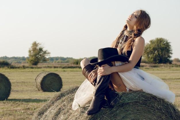 仕事の後に休んでいる干し草の山でカウボーイハットとドレスのセクシーな女性