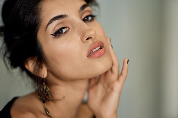 Сексуальная женщина с вечерним макияжем и модным крупным планом портрета серьги