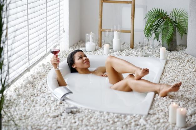 ミルクとお風呂で飲み物のガラスを持つセクシーな女性。バスタブの女性、スパの美容とヘルスケア、バスルームのウェルネストリートメント、背景の小石とキャンドル