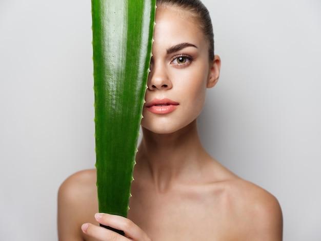 緑のアロエの葉の裸の肩の透明な肌を持つセクシーな女性