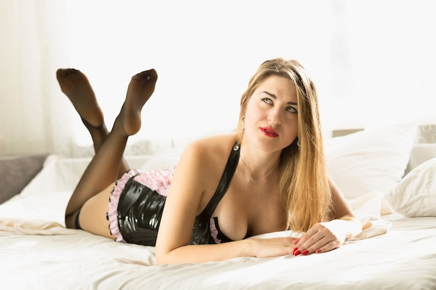ウィンドウの横にあるベッドに横になっているランジェリーの長い髪のセクシーな女性