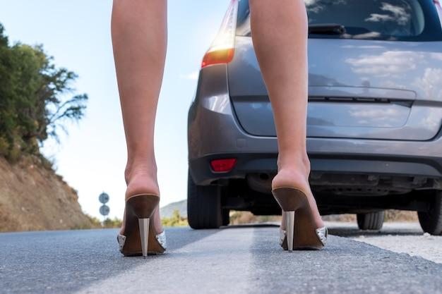 Сексуальная женщина с длинными ногами, стоящая рядом с машиной по сигналу тревоги