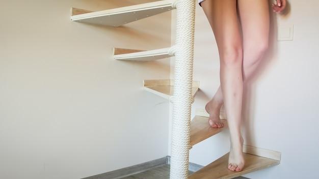 Сексуальная женщина с длинными ногами спускается по винтовой деревянной лестнице дома