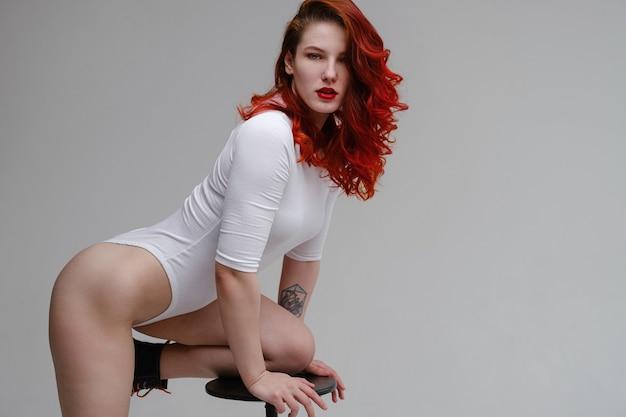 Сексуальная женщина с длинными красными волосами, позирует в белом белье на фоне белой студии. оздоровление, удаление волос, концепция ухода за телом. йога и тренажерный зал, настоящая красота и позитив для тела