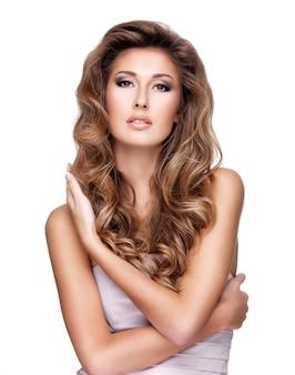 化粧をしたセクシーな女性は彼女の美しい長いウェーブのかかった髪に触れます。白で隔離