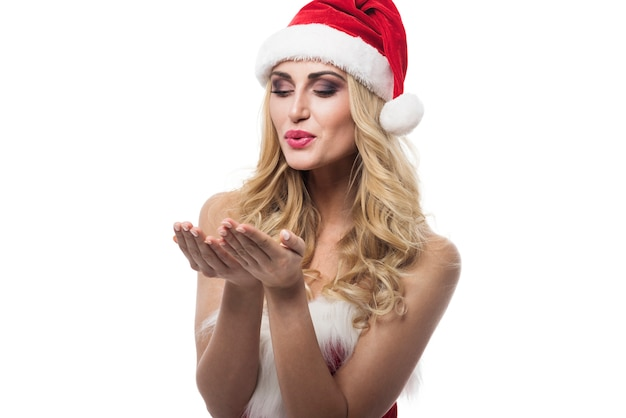 Sexy woman with santa hat posing on white wall