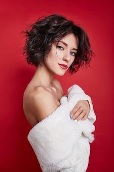 빨간 배경에 흰색 스웨터를 입은 짧은 머리를 가진 섹시한 여자. 젖은 헝클어진 검은 머리와 밝은 화장, 짧은 머리, 미용 및 헤어 케어를 갖춘 완벽한 소녀. 벌거 벗은 어깨 여성