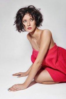Sexy woman with short hair. girl posing in a red sweater
