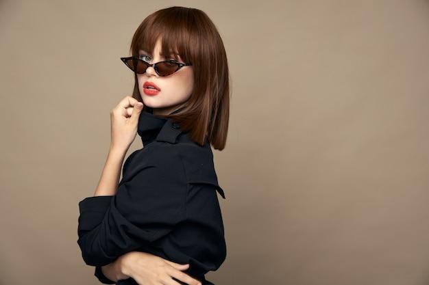 セクシーな女性は黒いコートに身を包んだエレガントな外観ベージュの孤立した壁